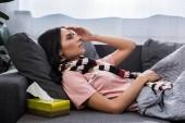 Fotografia giovane donna ammalata che misurare la temperatura con il termometro elettrico sul divano