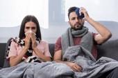 krankes junges Paar sitzt mit Serviette und Eisbeutel zusammen auf Couch und blickt in die Kamera