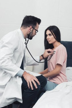 confident young doctor listening breath of female patient