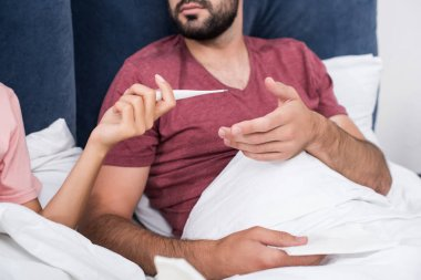 cropped shot of woman passing electric thermometer to her sick boyfriend in bed