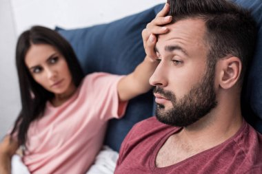 young woman touching forehead of sick husband while sitting in bed