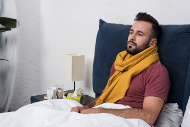 depressed sick young man lying in bed and looking away