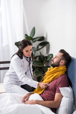 female doctor using stethoscope to listen to patients breath while he lying in bed