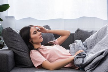 young woman suffering from headache while lying on couch