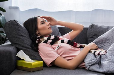 sick young woman measuring temperature with electric thermometer on couch