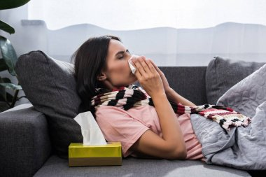 diseased young woman sneezing into paper napkin on sofa
