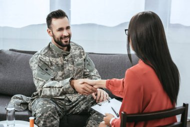 smiling soldier shaking hand of psychiatrist during therapy session