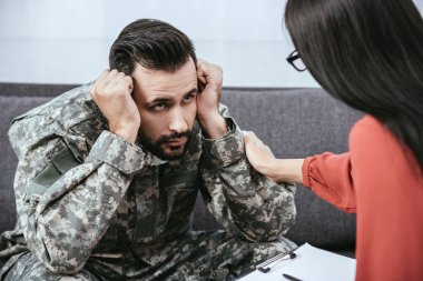 depressed soldier with post traumatic syndrome looking at psychiatrist during session