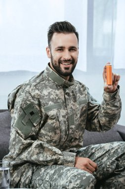 Happy young soldier holding plastic jar of pills and looking at camera stock vector