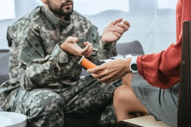 Cropped shot of soldier in uniform with ptsd talking to psychiatrist at therapy session while she holding jar of pills stock vector