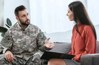 soldier in uniform with ptsd talking to psychiatrist at therapy session