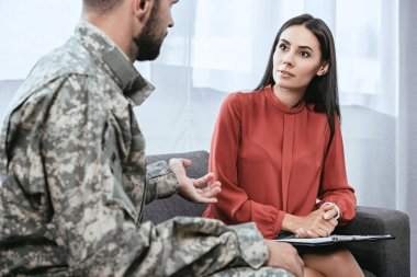 depressed soldier with ptsd talking to psychiatrist at therapy session