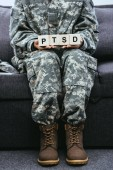 cropped shot of female soldier in military uniform sitting on couch and holding wooden cubes with PTSD sign