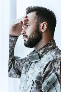 Depressed army man in military uniform with post-traumatic stress disorder touching his head and looking away stock vector