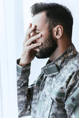 side view of depressed army man in military uniform with post-traumatic stress disorder