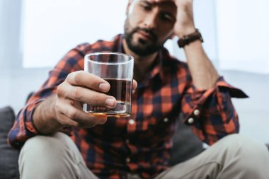 close-up shot of depressed young man with glass of whiskey