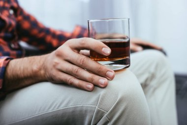cropped shot of young man holding glass of whiskey