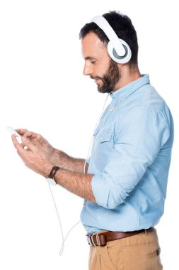 side view of bearded man listening music and using smartphone isolated on white