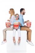 Fotografie family eating popcorn sitting on white cube isolated on white