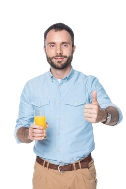 man holding glass with orange juice and showing thumb up isolated on white