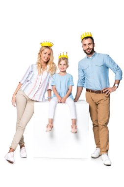 happy family with cardboard crowns sitting on white cube isolated on white