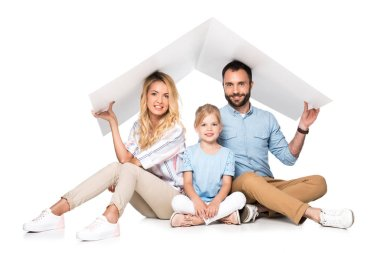 parents with daughter holding white roof over heads isolated on white, family insurance concept