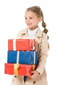Fotografia bambino sorridente in cappotto beige che tengono i regali, isolati su bianco