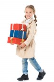 adorable child in autumn coat holding gift boxes, isolated on white