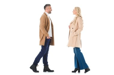 Smiling couple posing in trendy beige coats, isolated on white stock vector
