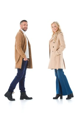 stylish couple posing in beige autumn coats, isolated on white