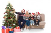 Fotografie happy family in santa hats sitting on sofa near christmas tree with presents, isolated on white