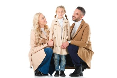 parents with daughter in beige autumn coats, isolated on white