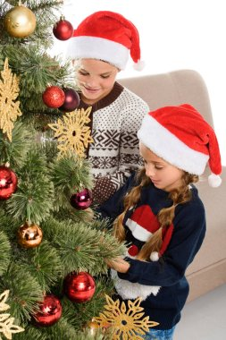 brother and sister in santa hat decorating christmas tree, isolated on white