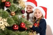 glückliche Geschwister in Weihnachtsmütze schmücken Weihnachtsbaum mit Kugeln