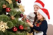 děti v santa hat zdobení vánočního stromu s míčky