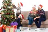 parents in santa hats looking at children decorating christmas tree, isolated on white