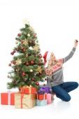 boldog asszony ül karácsonyfa, ajándékok, és figyelembe selfie a smartphone, elszigetelt fehér