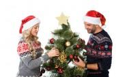 nádherný pár v santa klobouky, zdobení vánočního stromu, izolované na bílém