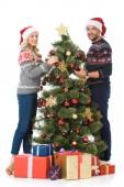 krásný pár, zdobení vánočního stromu s dárkové krabičky, izolované na bílém