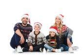 happy parents with children sitting in christmas sweaters and santa hats, isolated on white