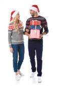 Paar in weihnachtspullover und Santa Hüte halten Geschenk-Boxen, isoliert auf weiss