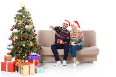 beautiful couple with cups of coffee and sitting on sofa near christmas tree with gifts, man pointing somewhere, isolated on white