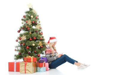 beautiful woman using smartphone and sitting near christmas tree with gifts, isolated on white