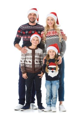 happy family with kids posing in christmas sweaters and santa hats, isolated on white