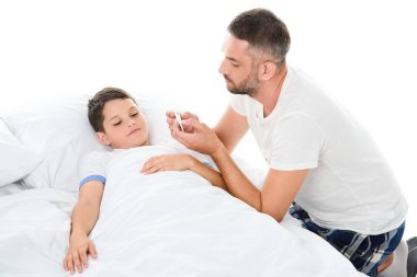 father looking at electronic thermometer while son with temperature lying in bed, isolated on white