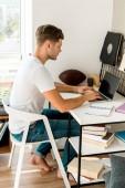 Fotografie Seitenansicht der junge Mann mit Laptop am Tisch zu Hause im Büro