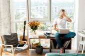 mladý muž v neformálním oblečení s notebookem pokrývající oči přitom sedí u okna doma