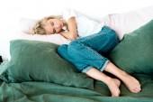 Fotografie mladá žena v neformálním oblečení spí na polštáři v posteli doma
