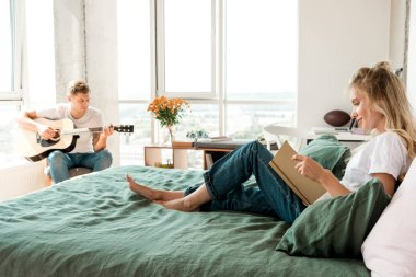 young woman reading book on bed while boyfriend playing acoustic guitar at home