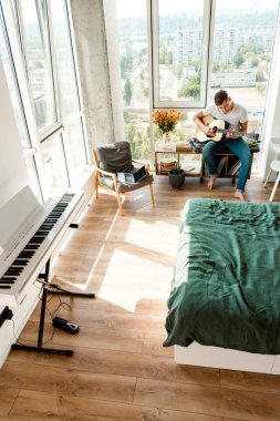 high angle view of young man playing acoustic guitar at home